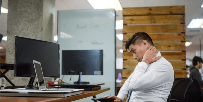 Man Having Neck Strain while Working in the Office